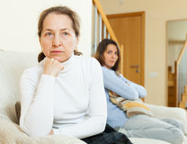 Mother and daughter after quarrel. Mature mother sitting offended on sofa at home after quarrel with teen daughter royalty free stock photography