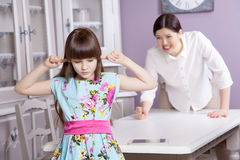 Mother and daughter quarrel because of overuse the tablet phone computer, tablet, etc.. Royalty Free Stock Image