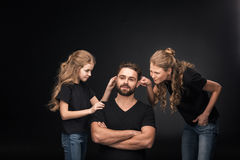 Mother and daughter quarreling at father sitting with crossed arms Stock Image