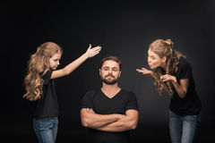 Mother and daughter quarreling at father sitting with crossed arms Stock Photos