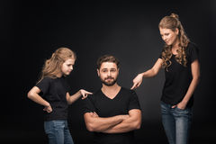 Mother and daughter quarreling at father sitting with crossed arms Royalty Free Stock Photo