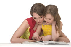 Mother and daughter read book. Mum and daughter sit at table and read book Stock Photo