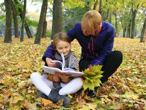 Mother and daughter read a book in the autumn park Royalty Free Stock Photos