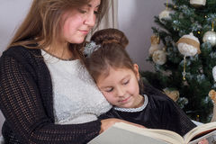 Mother and daughter read a book at fireplace on Christmas eve. Stock Photos