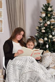 Mother and daughter read a book at fireplace on Christmas eve. Stock Image