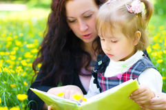 Mother with daughter read a book. On the meadow Royalty Free Stock Photography