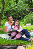 Mother and daughter read book Stock Images