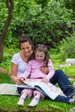 Mother and daughter read book outdoors Stock Photo