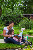 Mother and daughter read book outdoors Royalty Free Stock Images