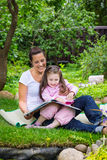 Mother and daughter read book outdoors Royalty Free Stock Photography