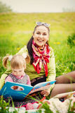 Mother with daughter read a book in the park Royalty Free Stock Photo