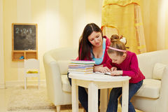 Mother and daughter read book, sitting at table Stock Photo