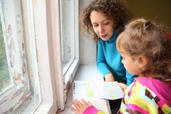 Mother with daughter read history near window Royalty Free Stock Photos