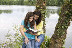 Mother and daughter reading. A book on the outdoors Stock Images