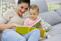 Mother and daughter reading baby book Royalty Free Stock Photos