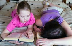 Mother and daughter reading in bed book Stock Images