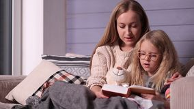 Mother and daughter reading bedtime story on sofa stock video