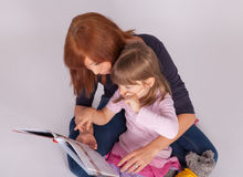 Mother and daughter are reading a book Stock Photos