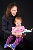 Mother with daughter reading book Stock Photos