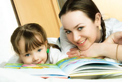 Mother and daughter reading a book. Young beautiful mother and her little daughter lie on the bed and read a book Royalty Free Stock Photo
