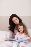 Mother and daughter reading a book on the bed Stock Images