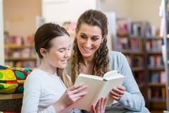 Mother and daughter reading a book in community center library. With fun Royalty Free Stock Photos