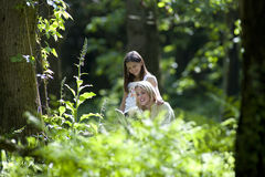 Mother and daughter (7-9) reading book in forest, smiling Stock Photos