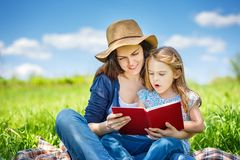 Mother and daughter reading book on green summer meadow. Mother and daughter enjoy reading book sitting on green meadow in the summer park royalty free stock photo