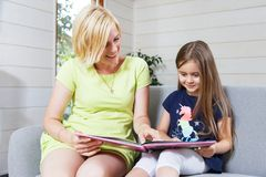 A Mother And Daughter Reading Book stock photos