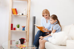 Mother and daughter reading book at home Royalty Free Stock Image