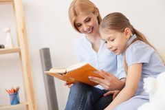 Mother and daughter reading book at home Royalty Free Stock Photo