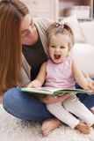 Mother and daughter reading a book Stock Photography