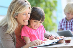 Mother and daughter reading book and laughing. Woman with daughter teaching how to read Royalty Free Stock Photography
