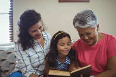 Mother and daughter reading book in living room Royalty Free Stock Photo