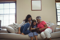 Mother and daughter reading book in living room Royalty Free Stock Photography