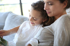 Mother and daughter reading book. Mom with little girl reading book in sofa Royalty Free Stock Photo