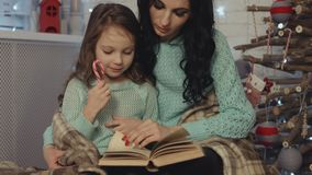 Mother and daughter reading the book near the wooden Christmas tree stock footage