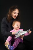 Mother with daughter reading book over black Royalty Free Stock Image
