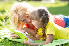 Mother and daughter reading a book at the park Stock Images