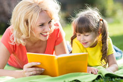 Mother and daughter reading a book at the park Stock Photos