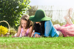 Mother and daughter reading book in the park Royalty Free Stock Photos