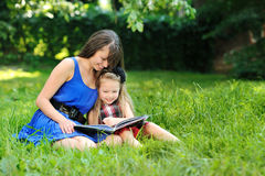 Mother and daughter reading book in a park Stock Images