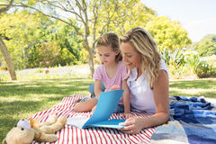 Mother and daughter reading book in park Royalty Free Stock Images