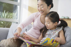 Mother With Daughter Reading Book On Sofa Royalty Free Stock Image