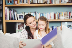 Mother and daughter reading book on sofa at home Stock Images