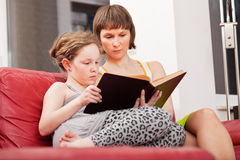 Mother and daughter reading book together. Mother and teenager daughter sitting on sofa together and reading an old book Stock Image
