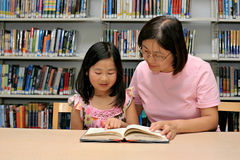 Mother and daughter reading book together Royalty Free Stock Image