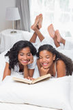 Mother and daughter reading book together on bed Royalty Free Stock Photography