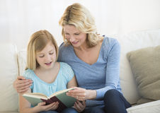 Mother And Daughter Reading Book Together On Sofa Stock Images