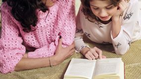 Mother and daughter reading book together, story before bedtime, close up royalty free stock photography